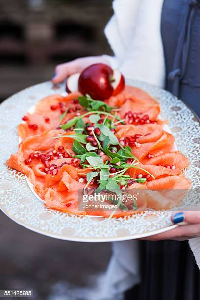 Person holding tray with smoked salmon and pomegranate seeds