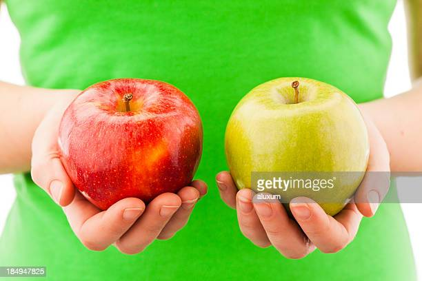 a person holding two apples in their hands - comparison stock pictures, royalty-free photos & images