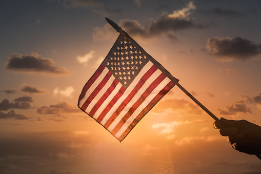 Person holding USA American flag on sunset background. 1188704306