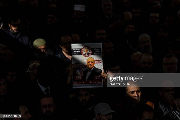 TOPSHOT A person holds a banner of Jamal Khashoggi during a symbolic funeral prayer for the Saudi journalist killed and dismembered in the Saudi...