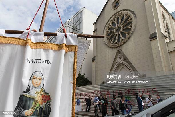 A person holds a banner picturing SainteRita as other stand in front of barriers blocking the access to the sainteRita church in Paris with an...
