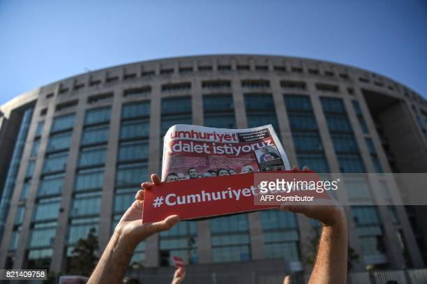 A person holds a banner reading 'Cumhuriyet will not be silenced' and a copy of daily opposition daily neswpaper Cumhuriyet reading 'We want Justice'...