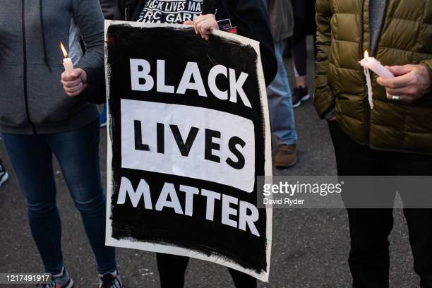 A person holds a Black Lives Matter sign during a vigil for Manuel Ellis a black man whose March death while in Tacoma Police custody was recently...