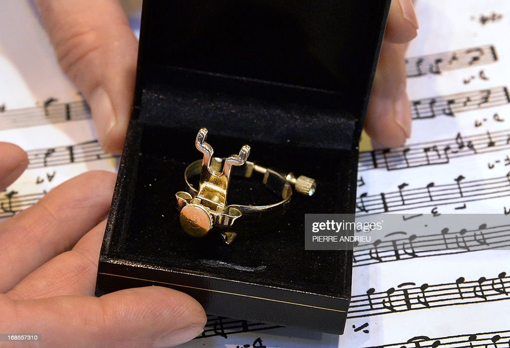 A person holds a box containing a brass ligature aimed at adjusting the reed of a saxophone or a clarinet in order to preserve the sound, an invention by Jean-Luc Vignaud, winner of the 2013 Concours Lepine (Lepine contest) during the Paris' Fair at the Porte de Versailles exhibition hall in Paris, on May 11, 2013. The competition was launched in 1901 by Louis Lepine, the city's police chief. ANDRIEU