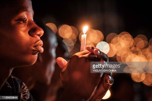 TOPSHOT A person holds a candle during a night vigil and prayer at the Amahoro Stadium as part of the 25th Commemoration of the 1994 Genocide in...