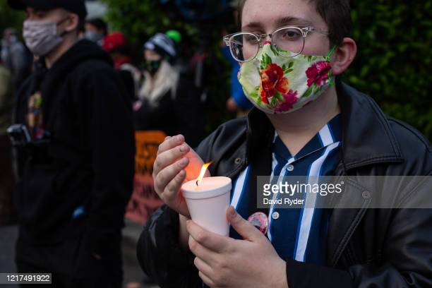 A person holds a candle during a vigil for Manuel Ellis a black man whose March death while in Tacoma Police custody was recently found to be a...
