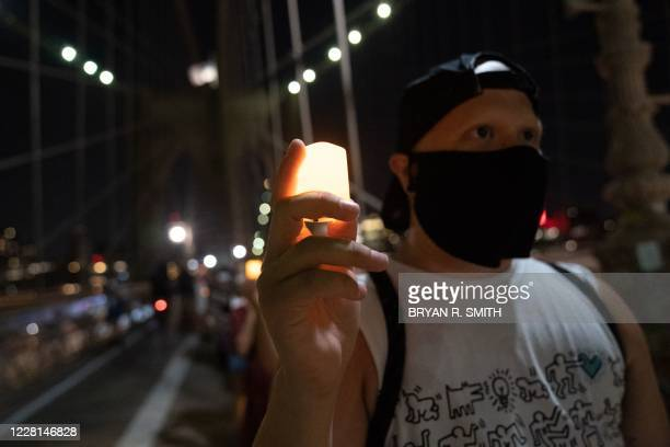 """Person holds a candle during the """"March for the Dead"""" across the Brooklyn Bridge, in memory of those who have died of COVID-19 and to protest the..."""