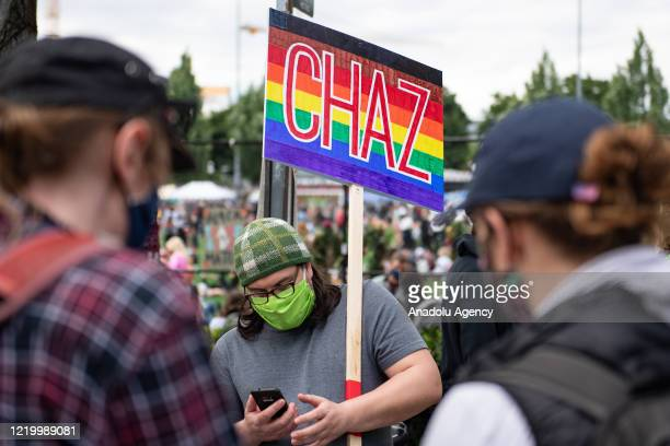 A person holds a CHAZ sign inside the âCapitol Hill Organized Protestâ formerly known as the âCapitol Hill Autonomous Zoneâ in Seattle Washington on...