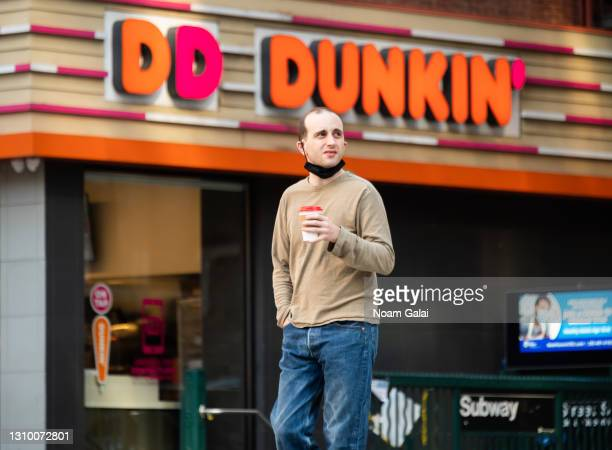Person holds a coffee cup outside Dunkin' Donuts in Hell's Kitchen amid the coronavirus pandemic on March 30, 2021 in New York City. After undergoing...
