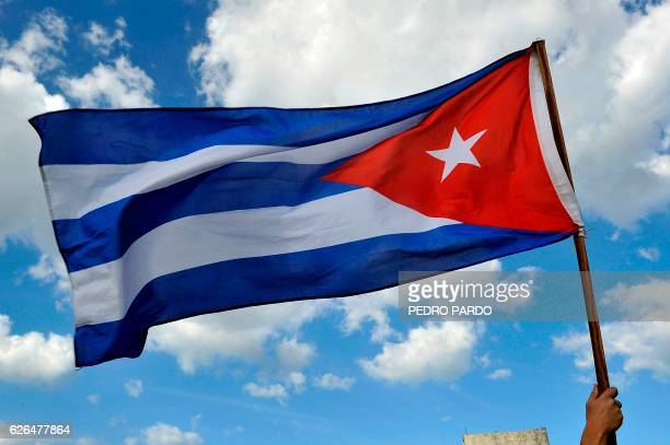 A person holds a Cuban national flag as Cubans arrive to pay their last respects to late revolutionary leader Fidel Castro at Revolution Square in...