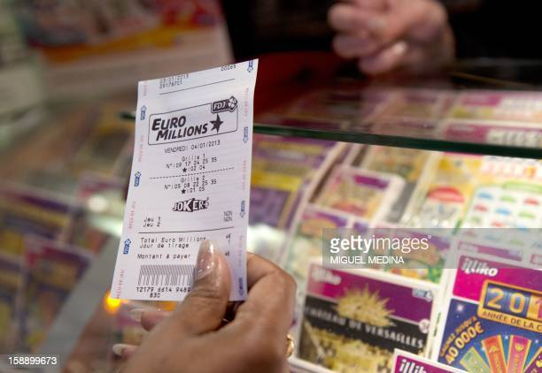 A person holds a EuroMillions ticket on January 3 2013 in Paris The Française des Jeux the operator of France's national lottery games announced on...