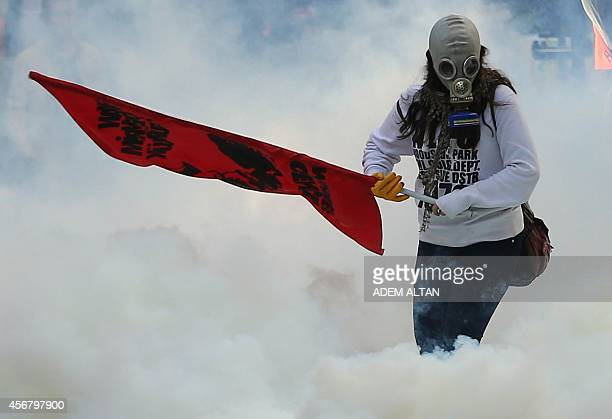 Person holds a flag as police uses tear gas and water cannon on October 7, 2014 in Ankara against demonstrators who protest against attacks launched...