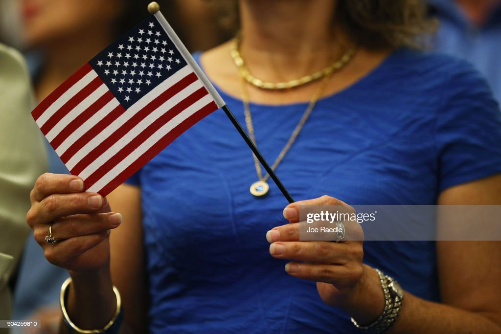 A person holds a flag as they are sworn in as an American citizen during a U.S. Citizenship & Immigration Services naturalization ceremony at the Hialeah Field Office on January 12, 2018 in Hialeah, Florida. 150 people from different countries around the world took part in the Oath of Allegiance.