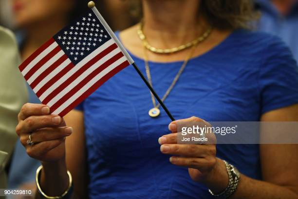 A person holds a flag as they are sworn in as an American citizen during a US Citizenship Immigration Services naturalization ceremony at the Hialeah...