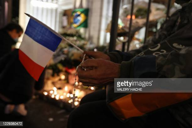 Person holds a French national flag and a rosary outside Notre-Dame de l'Assomption Basilica in Nice on October 31 to pay tribute to the victims two...