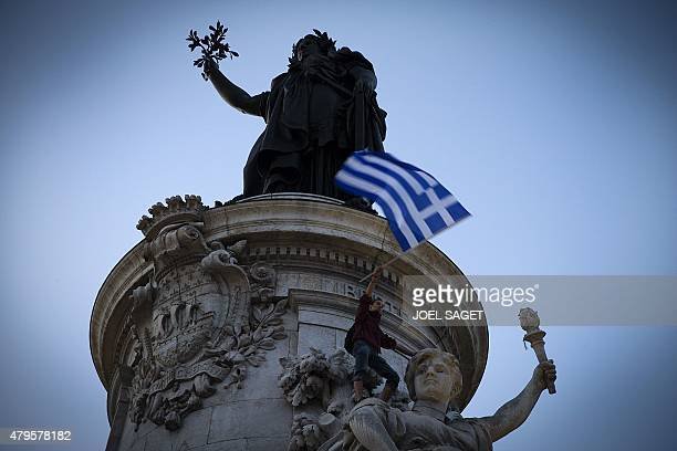 A person holds a Greek national flag during a rally in support of the people of Greece on the Republique square in Paris on July 5 as Greeks vote in...