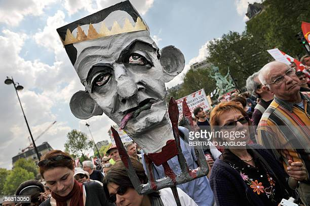 A person holds a head featuring French president Nicolas Sarkozy during the traditional May Day demonstration on May 1 2009 in Paris as leftwing...
