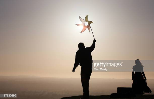 A person holds a holds a windmill as people watch the sun rise as they join in a Beltane dawn celebration service in front of St Michael's Tower on...