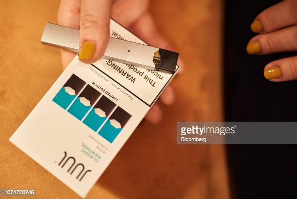 A person holds a Juul Labs Inc ecigarette next to a package of Classic Menthol pods in this arranged photograph taken in the Brooklyn Borough of New...