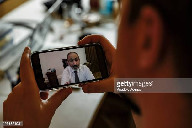 Person holds a mobile phone screen showing Prime Minister of Armenia, Nikol Pashinyan speaking during a live broadcast over Facebook after the...