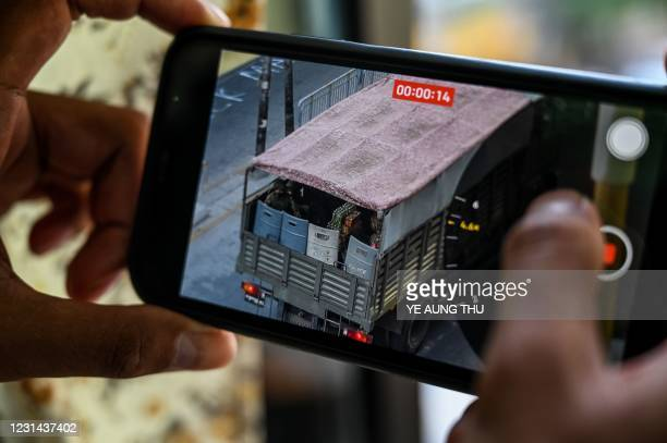 Person holds a mobile phone showing a video of soldiers looking out from a truck in Yangon on February 28 as security forces continue to crackdown on...