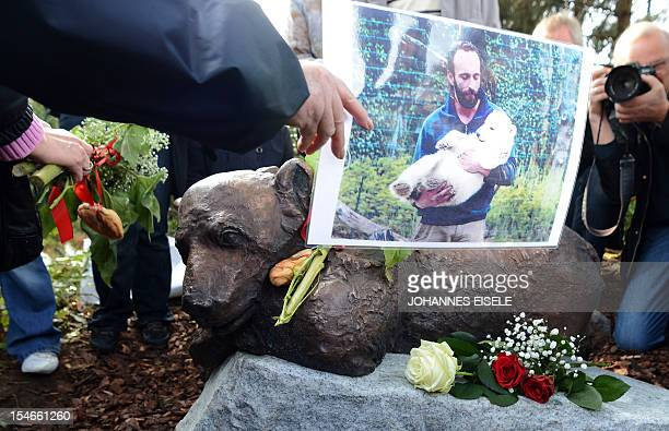 A person holds a photograph showing animal keeper Thomas Doerflein with polar bear Knut in front of the just unveiled sculpture Knut The Dreamer at...