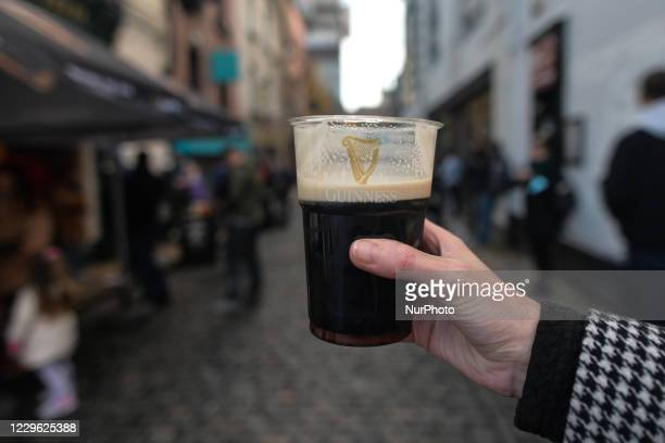 Person holds a pint of Guinness in a plastic cup seen outside The Ha'Penny Bridge Pub in the center of Dublin. On Saturday, November 14 in Dublin,...