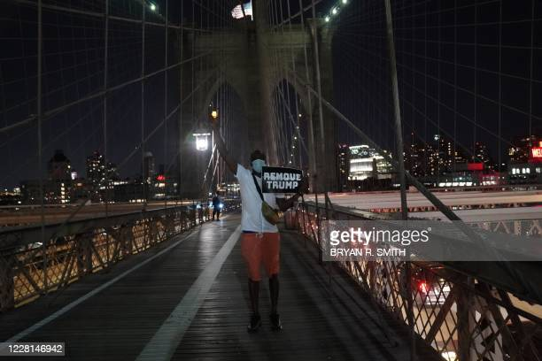 """Person holds a placard and a candle during the """"March for the Dead"""" across the Brooklyn Bridge, in memory of those who have died of COVID-19 and to..."""