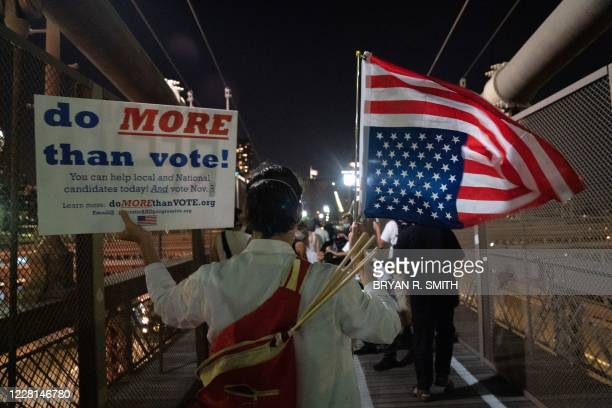 """Person holds a placard and an upside down US flag during the """"March for the Dead"""" across the Brooklyn Bridge, in memory of those who have died of..."""