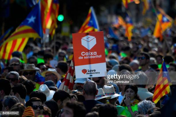 A person holds a placard depicting a ballot box with a message reading in Catalan Box of solidarity as people wave 'Esteladas' during a...