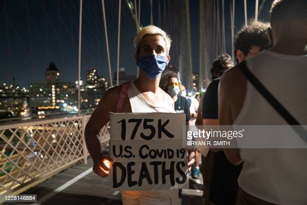 """Person holds a placard during the """"March for the Dead"""" across the Brooklyn Bridge, in memory of those who have died of COVID-19 and to protest the..."""