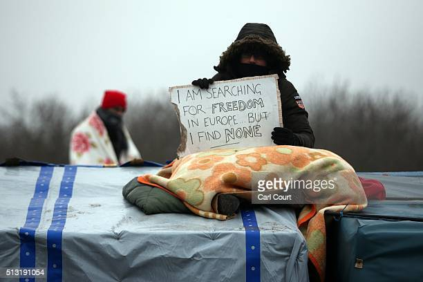 A person holds a placard on the roof of a hut as police and demolition workers clear the 'jungle' migrant camp on March 01 2016 in Calais France...