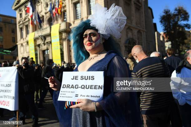 A person holds a placard reading I am a drag queen during a demonstration called by owners of restaurants and night clubs to call for the ease of the...