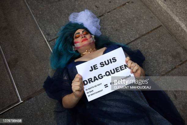 A person holds a placard reading I am drag queen as he lies on the ground during a demonstration called by owners of restaurants and night clubs to...