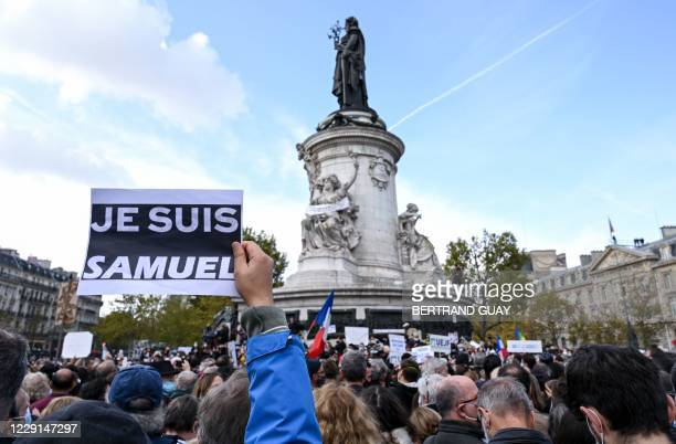 """Person holds a placard reading """"I am Samuel"""" as people gather on Place de la Republique in Paris on October 18 in homage to history teacher Samuel..."""
