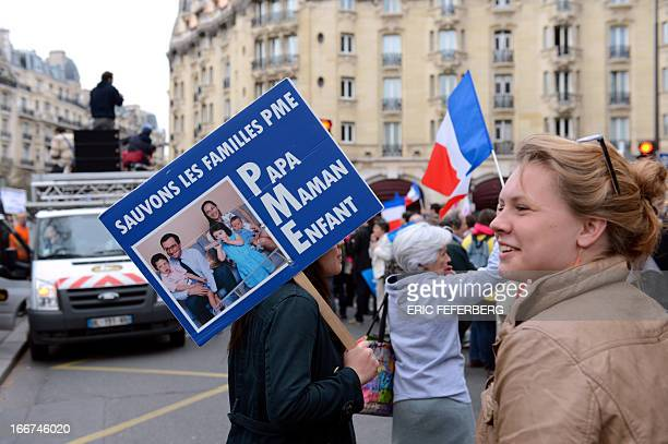 A person holds a placard reading Let us save the 'Dad Mom Child' families among supporters of the antigay marriage movement La Manif Pour Tous...