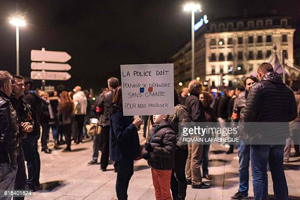 A person holds a placard which translates as 'Police should defend itself with no fear to protect us' on October 26 2016 in Lyon during a...