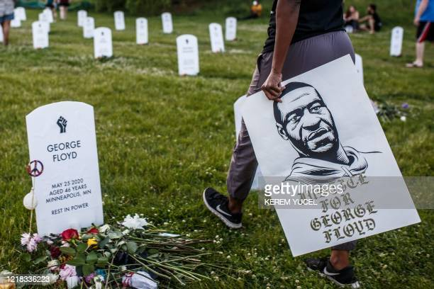 Person holds a placard with a portrait of George Floyd during a candlelight vigil at an installation created by Anna Barber and Connor Wright called...