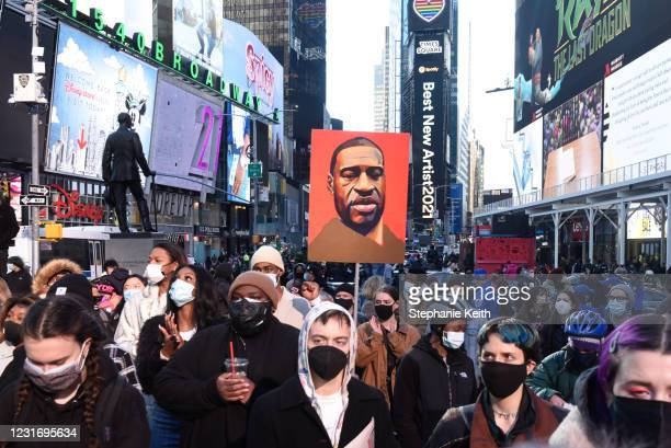 Person holds a placard with George Floyd's face during a protest to mark the one year anniversary of Breonna Taylor's death on March 13, 2021 in New...