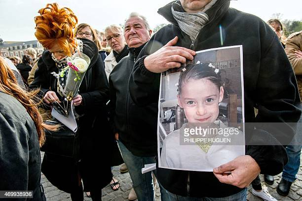 A person holds a portrait during a march on April 16 2015 in Calais northern France in homage to a nineyearold girl who was killed a day before A...