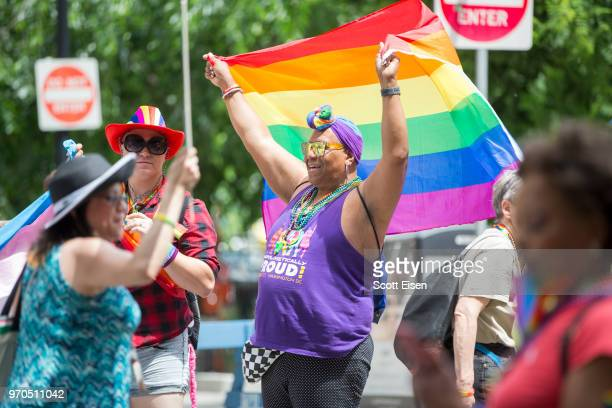 A person holds a pride flag as the 2018 Boston Pride Parade passes on Clarendon St on June 9 2018 in Boston Massachusetts