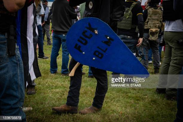 """Person holds a shield that reads """"Fuck BLM"""" during a Proud Boys rally at Delta Park in Portland, Oregon on September 26, 2020. - Far-right group..."""