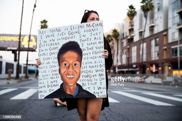 A person holds a sign at a candlelight vigil to demand justice for Elijah McClain on the one year anniversary of his death at The Laugh Factory on...