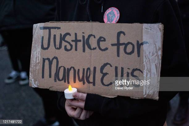 A person holds a sign during a vigil for Manuel Ellis a black man whose March death while in Tacoma Police custody was recently found to be a...
