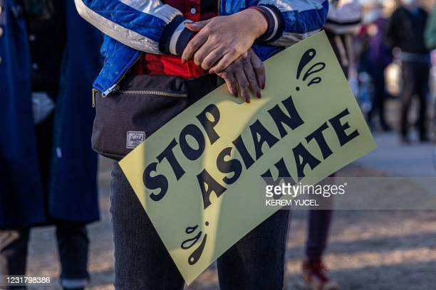 "Person holds a sign during the ""Asian Solidarity March"" rally against anti-Asian hate in response to recent anti-Asian crime on March 18, 2021 in..."