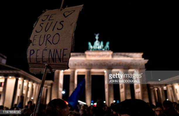 """Person holds a sign reading """"I am European"""" in French during a flashmob to mark Brexit in front of Berlin's Brandenburg Gate on January 31, 2020. -..."""
