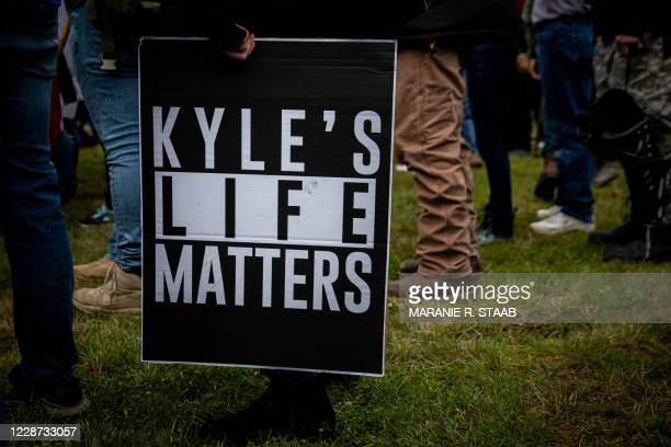 """Person holds a sign that reads """"Kyle's Life Matters"""", a reference to Kyle Rittenhouse, as several hundred members of the Proud Boys and other similar..."""