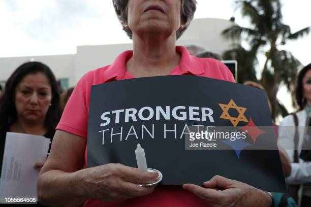 A person holds a sign that reads 'Stronger than Hate' as she joins with others for a CommunityWide Solidarity Vigil at the Holocaust Memorial Miami...