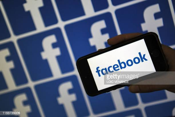 A person holds a smartphone showing the logo of the US online social media and social networking service Facebook on July 4 2019 in Nantes