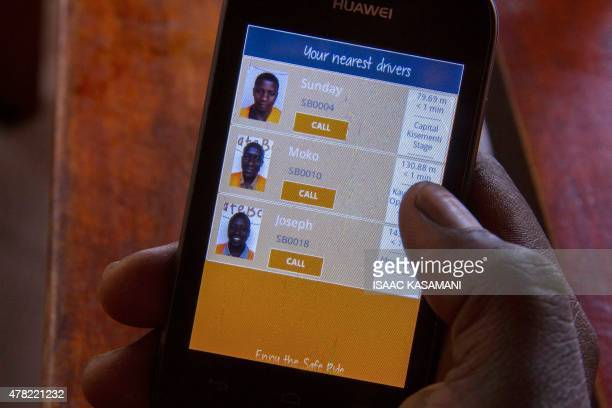 A person holds a smartphone with Safeboda application on March 6 2015 in Kampala Safebodas backers are hoping the service will do more than just...